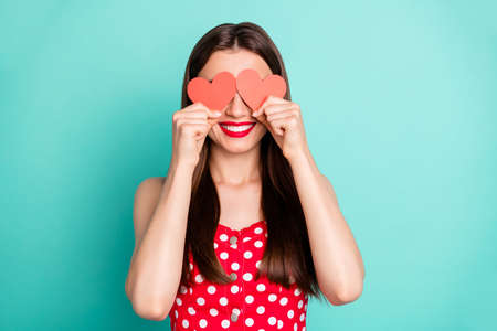 Portrait of charming lady hiding her eyes face with papercard heart wearing polka dot skirt dress isolated over teal turquoise background