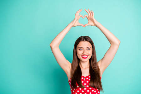 Portrait of cute lady smiling showing heart shaped sign wearing polka dot dress skirt isolated over teal turquoise background