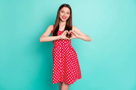 Portrait of charming millennial showing her feelings care making heart with fingers wearing polka dot skirt dress isolated over teal turquoise background