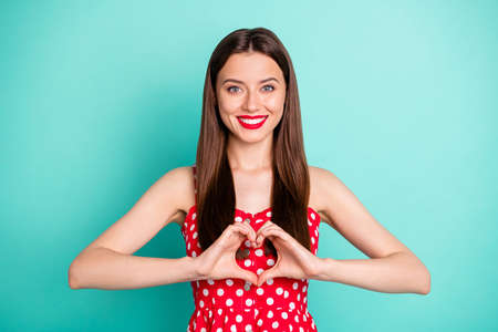 Portrait of lovely girl hsoiwing her figure shape heart with fingers smiling wearing polka dot skirt dress isolated over teal turquoise background 스톡 콘텐츠
