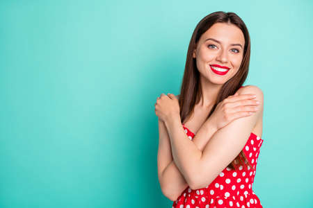 Portrait of cute girl hugging with toothy smile wearing polka dot dress skirt clothing isolated over teal turquoise background 스톡 콘텐츠
