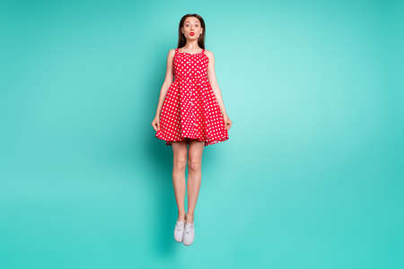 Full length photo of pretty girl jumping with her lisp pouted plump wearing polka dot skirt dress isolated over teal turquoise green background