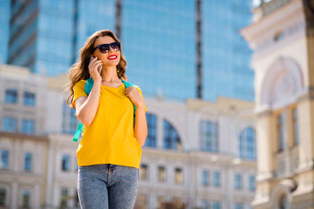Portrait of her she nice attractive lovely charming pretty cheerful cheery dreamy girl talking on cell wandering abroad downtown on fresh air sight seeing outdoors