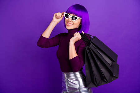 Photo of stylish lady holding many packs in hands dressed in trendy outfit isolated purple background 스톡 콘텐츠
