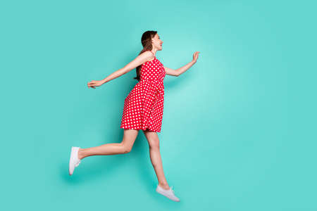 Fulll body profile side photo of lovely girl running after bargains wearing polka dot skirt dress isolated over teal turquoise background