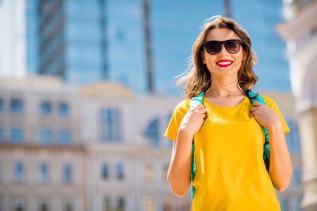 Portrait of her she nice attractive lovely charming cheerful cheery glad dreamy girl wearing colorful yellow bright t-shirt traveling around the world globe outdoors