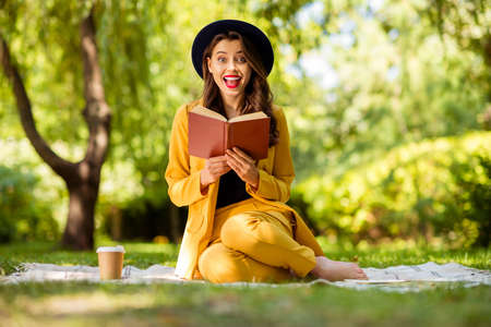 Portrait of her she nice-looking attractive lovely charming pretty trendy cheerful cheery excited crazy overjoyed wavy-haired girl sitting on cover reading cool interesting book on fresh air outdoors