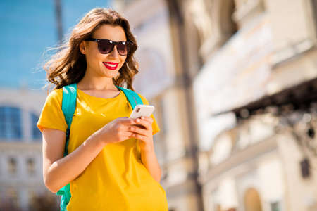 Portrait of her she nice attractive lovely winsome pretty cheerful cheery girl wearing colorful yellow bright t-shirt browsing internet online web service outdoors