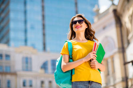 Low below angle view portrait of her she nice attractive lovely dreamy cheerful cheery wavy-haired girl enjoying traveling abroad carrying learn materials in downtown center outdoor