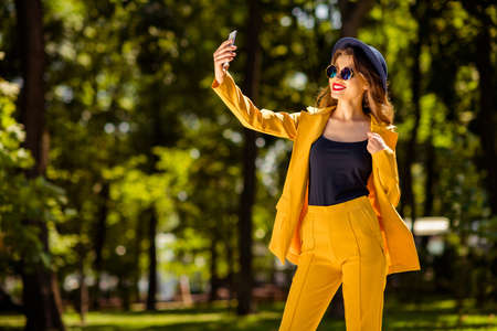 Portrait of her she nice-looking gorgeous attractive lovely charming pretty cheerful cheery confident trendy fashionable girl taking making selfie in green forest wood outdoors