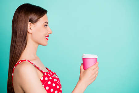 Profile side photo of lovely millennial holding disposable mug looking with toothy smile wearing polka dot dress isolated over teal turquoise background