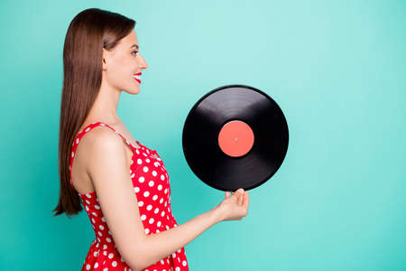 Profile side photo of lovely girl holding gramophone disc wearing polka dot dress skirt isolated over teal turquoise background 스톡 콘텐츠