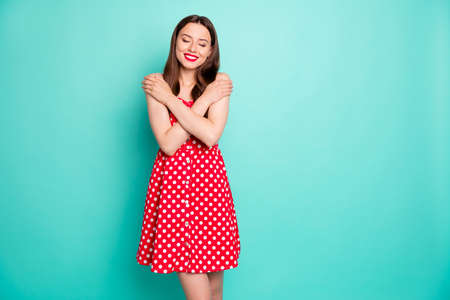 Portrait of cute lady with her eye closed smiling wearing polka dot skirt dress isolated over teal turquoise background 스톡 콘텐츠