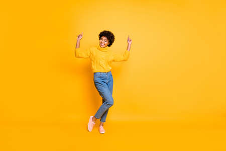 Full length body size photo of curly crazy funny overjoyed girlfriend dancing rejoicing wearing, jeans denim sweater footwear isolated over yellow background vivid color