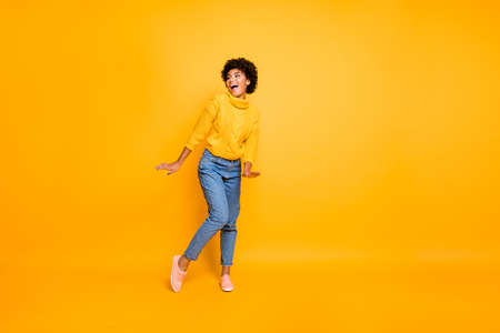 Full length body size photo of charming cute nice funny black girlfriend, dancing spending her free time wearing jeans denim pullover isolated vivid color background 写真素材