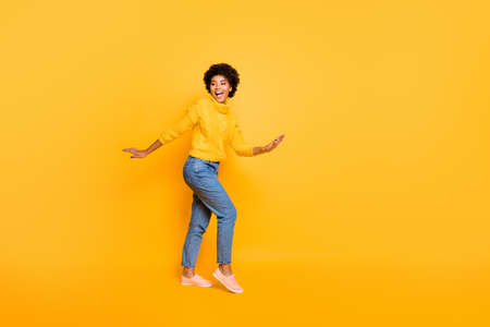 Full length body size view of nice attractive charming lovely cheerful, cheery funky wavy-haired girl having fun time isolated over bright vivid shine vibrant yellow color background