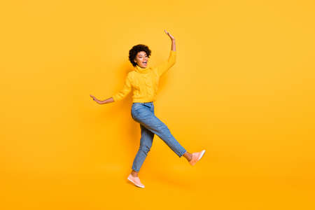 Full length body size view of nice attractive cheerful cheery funky childish careless, wavy-haired girl having fun free time isolated over bright vivid shine vibrant yellow color background 写真素材
