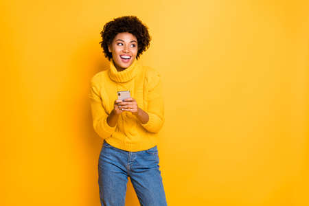 Copyspace photo of charming cute nice gorgeous fascinating attractive blogger black lady wearing jeans denim jumper rejoicing with new phone in her hands isolated over vivid color background Imagens