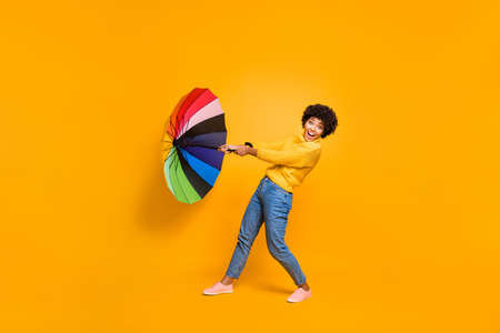 High wind is not an obstacle on the way to your goal concept. Side profile full body photo of funny careless carefree optimistic hipster person trying to hold parasol in hand isolated vivid background
