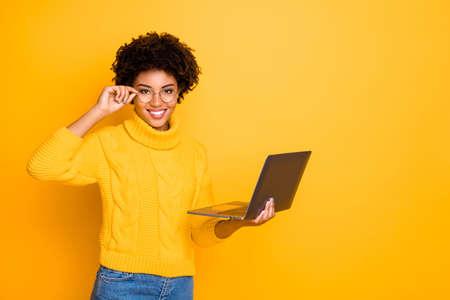 Foto van een charmante, schattige, zwarte, krullende, aantrekkelijke vriendin die haar laptop en een bril vasthoudt op zoek naar iets dat leuk vindt om jeans te dragen, denim gele trui, geïsoleerde levendige kleurenachtergrond Stockfoto