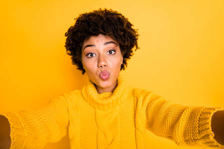 Photo of stylish trendy cheerful nice cute fascinating girlfriend pouting her lips kissing someone taking selfie wearing sweater isolated over yellow vivid color background Stock Photo