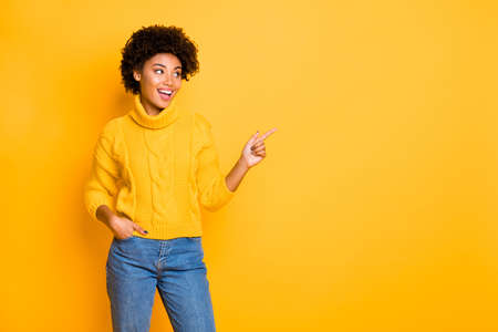 Portrait of her she nice attractive lovely charming cute pretty trendy cheerful confident wavy-haired girl pointing aside ad advert isolated over bright vivid shine vibrant yellow color background Standard-Bild
