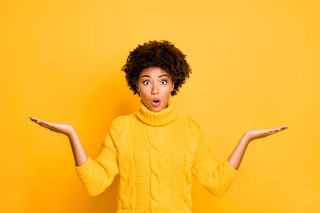 Photo of dark skin lady holding two new products on arms not believe low prices wear knitted pullover isolated yellow background Stock Photo
