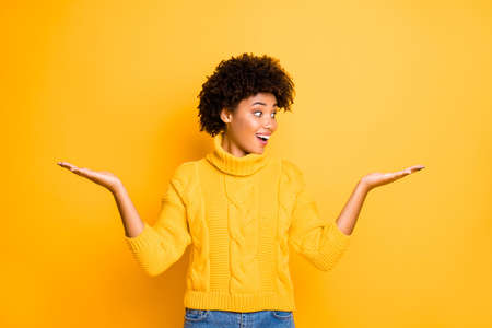 Dame de vente à la peau foncée tenant deux nouveaux produits sur les bras proposant les meilleurs prix porter un pull tricoté chaud isolé sur fond de couleur jaune