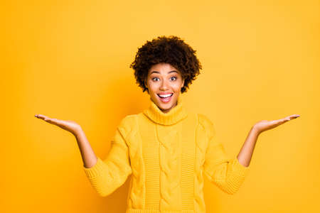Photo of dark skin sales lady holding two new products on arms proposing best prices wear warm knitted pullover isolated yellow background Stock Photo