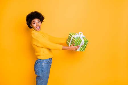 Concepto de tiempo de Navidad X-mas. Foto de asombrado asombrado adolescente obteniendo un enorme contenedor con regalo secreto en el interior envuelto en papel punteado verde vistiendo jeans aislados de fondo de color brillante