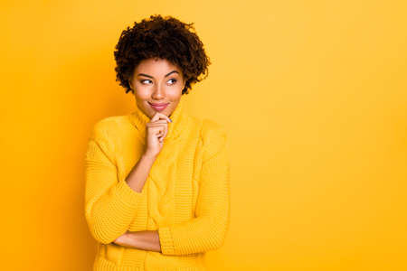 Copyspace photo of cheerful cute nice girlfriend smiling cunningly planning something wearing yellow knitted jumper while isolated over vibrant color background