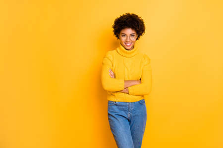 Copyspace photo of cheerful cute nice fascinating gorgeous attractive business black lady standing in jeans denim with arms crossed wearing yellow pullover isolated over vibrant color background