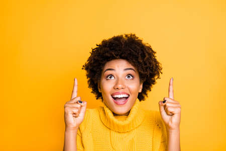 Photo of dark skin pretty lady indicating index fingers up to empty space on cool placard wear warm knitted jumper isolated yellow background