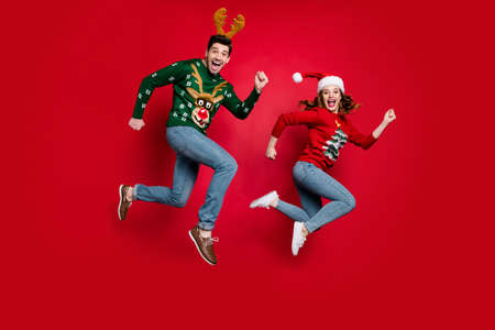 Full length photo of jumping couple excited by x-mas prices hurry, buy costumes wear ugly ornament jumpers isolated red color background
