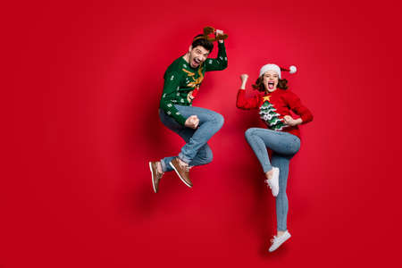 Full body photo of amazed jumping couple excited by x-mas prices, wear ugly ornament jumpers and headwear isolated red color background