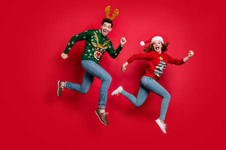 Full length photo of crazy jumping couple excited by x-mas discounts, prices wear ugly ornament jumpers isolated red color background