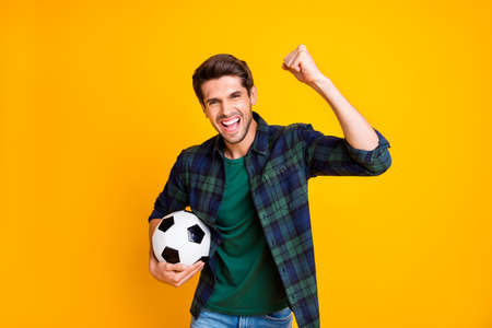 Photo of cool guy with white and black football ball playing cheerleader pole yelling words of support wear casual plaid shirt isolated yellow color background