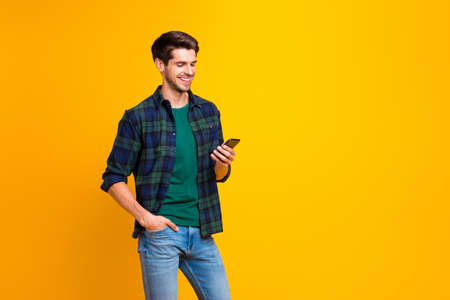 Photo of blogger guy holding telephone in hands checking subscribers wear casual checkered shirt and jeans isolated yellow color background