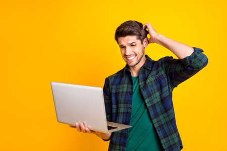 Photo of stressed guy with notebook in hands read bad investors reaction on startup, plan wear casual checkered shirt isolated yellow color background
