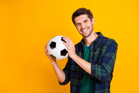 Photo of cool guy with white and black football ball excited to begin match wear casual plaid shirt isolated yellow color background Stockfoto