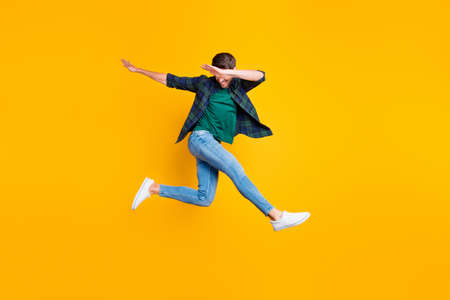Full body photo of cheerful content dream funky man jump have fun dance like true clubber enjoy summer vacation wear denim jeans sneakers checked green shirt isolated over yellow color background 免版税图像