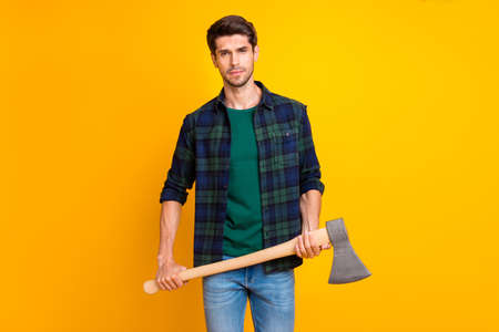 Photo of serious guy looking without smile ready to use big ax which hold in strong arms wear casual plaid shirt isolated yellow color background