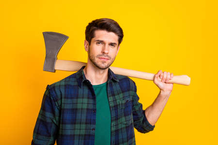 Photo of criminal guy looking without smile on enemy ready to use big ax wear casual plaid shirt isolated yellow color background