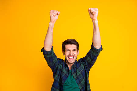 Photo of cool guy watching football game raising fists supporting favorite team wear casual plaid shirt isolated yellow color background Stockfoto