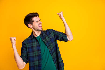 Photo of cool guy worried about football game raising fists supporting team wear casual plaid shirt isolated yellow color background Stockfoto