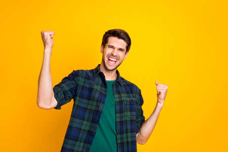 Photo of amazing guy worried about football game raising fists supporting team wear casual plaid shirt isolated yellow color background Stockfoto