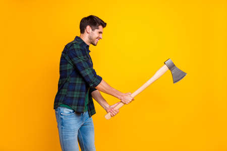 Profile photo of cool guy in process of cutting wooden materials with big ax wear casual plaid shirt isolated yellow color background