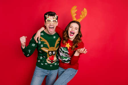 Photo of excited pair lady and guy chilling at newyear theme costume party wear funky knitted pullovers with ornaments isolated red color background