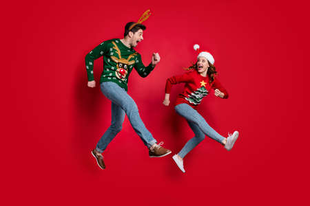 Full body photo of excited jumping couple rushing for x-mas discounts wear ugly ornament jumpers isolated red color background Banco de Imagens