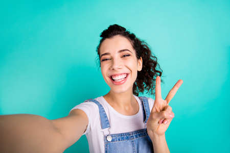 Self-portrait of her she nice attractive charming winsome cheerful cheery wavy-haired girl wearing casual showing v-sign isolated on bright vivid shine green turquoise background Archivio Fotografico